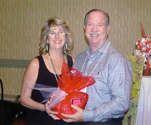 Anne Adams Goodwin presenting a raffle prize to Joe Baima.