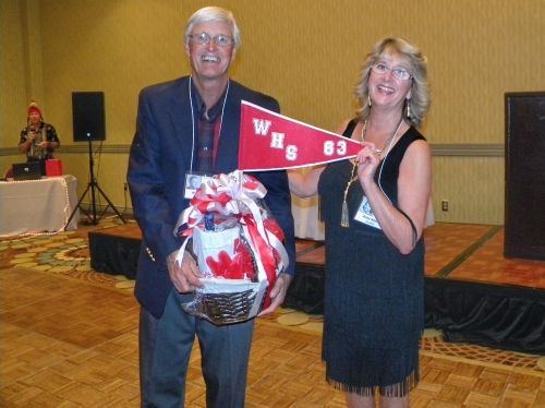 Bill Heck and Anne Adams Goodwin presenting Bill with one of many prizes donated by classmates and raffled off to those