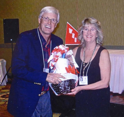 Anne Adams Goodwin presenting a raffle prize to Bill Heck.
